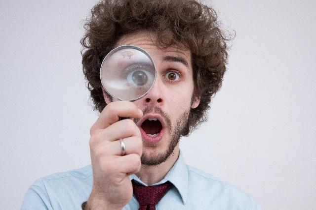 虫眼鏡を使う外国人